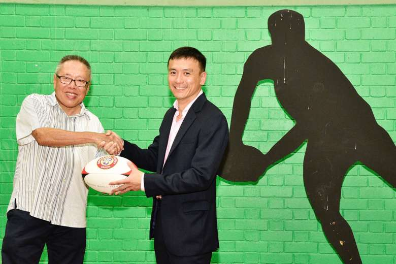 Low Teo Ping, (left) the outgoing president of the Singapore Rugby Union, shaking hands with his successor Terence Khoo,